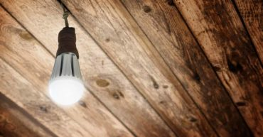 New LED light bulb replacing old bulb in an eco-friendly workplace