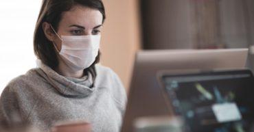 Femme masquée devant son ordinateur